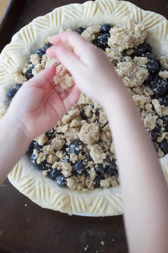 crumbling streusel over blueberry pie