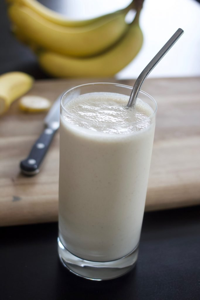 "banana peanut butter smoothie ""milkshake"" in a glass with bananas behind it"
