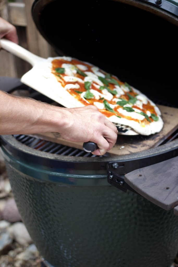 margherita pizza being transferred to grill
