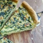 close up of sliced deep dish spinach quiche