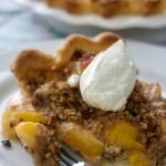 sliced fresh peach pie with whipped cream