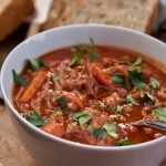 slow cooker beef & barley soup in a bowl with bread